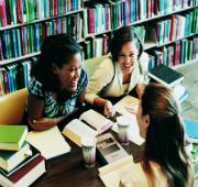 3 females at a table in a library